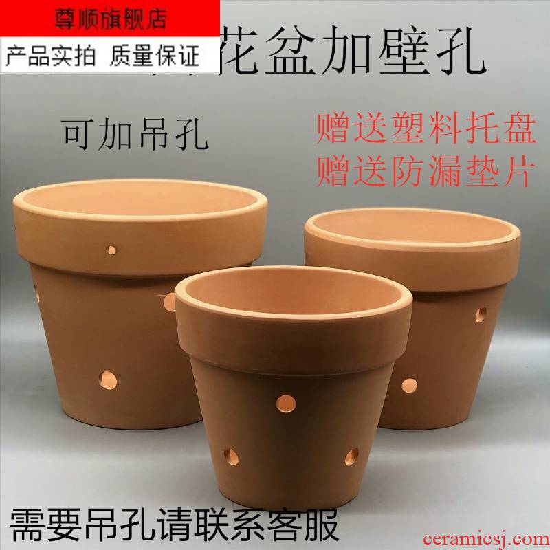 The Red clay flowerpots hanging wall made of baked clay porous coarse pottery and mud holes of large diameter orchid pot of money plant flower pot water through